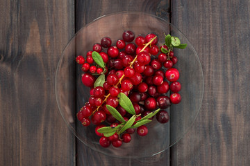 cowberries and red currants in a glass plate, top view