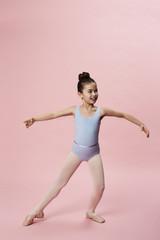 Young girl ballet dancing in pink studio