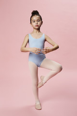 Young ballerina dancing in pink studio, portrait