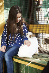 Girl petting rabbit in park