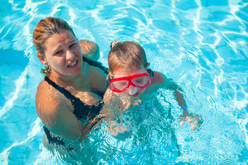 Mother teaches daughter to swim
