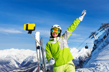 Happy skier woman take selfie with phone on stick