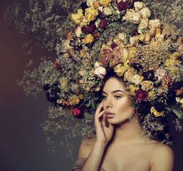 Beauty fashion female portrait with large garland dried flowers.