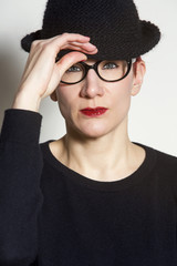 portrait of woman with black hat and glasses