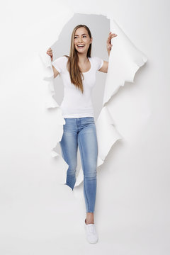 Young woman emerging from torn paper, smiling