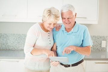Senior couple laughing using tablet in kitchen
