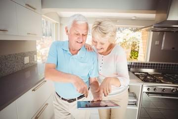 Happy senior couple holding digital tablet in kitchen