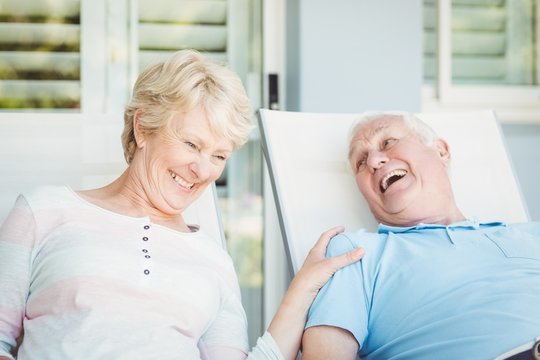 Happy senior couple relaxing on lounge chair