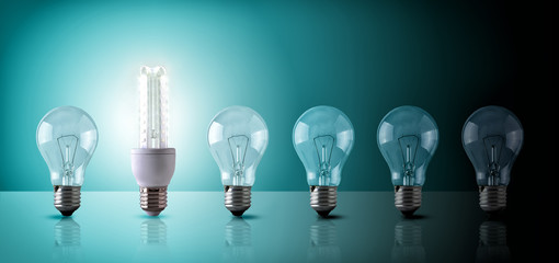 Energy saving concept with light bulbs sequence on blue-green ba