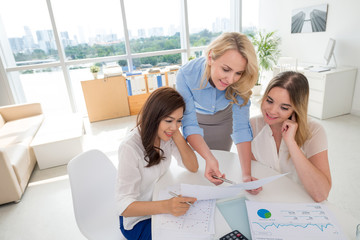 Business ladies examining document with financial data