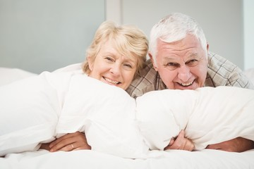 Happy senior couple resting on bed