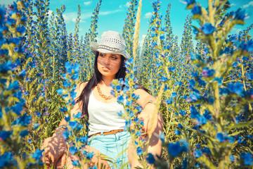 Beautiful cowboy woman posing in country field