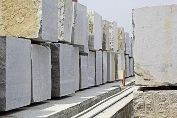 Huge Indian granite blocks stacked in a stone processing factory for cutting and polishing into flooring slabs used in building construction.