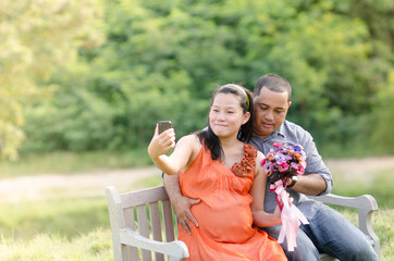 Selfie Asian Couple Expecting Pregnancy sitting on bench in the