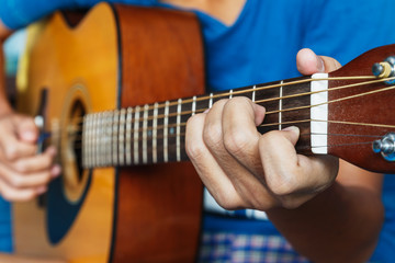 The boy's hands playing acoustic guitar, close up