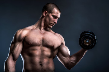 portrait of a young powerful bodybuilder lifting dumbbells