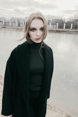 portrait of a beautiful young blonde woman in a black jacket on the street, cloudy