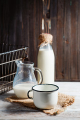 milk in the bottle , jug and cup on the wooden background