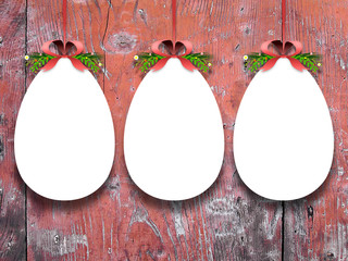 Close-up of three hanged Easter egg blank frames with red ribbons against red scratched wooden boards background