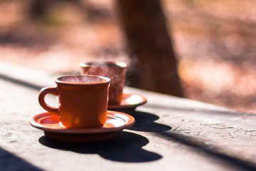 two cups of hot tea on wood background in autumn
