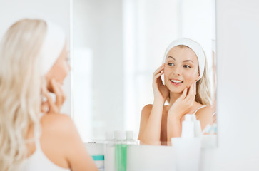 woman in hairband touching her face at bathroom