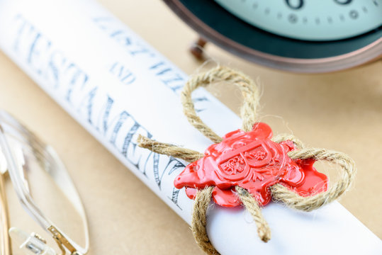 Rolled up scroll of last will and testament fastened with natural brown jute twine hemp rope, sealed with sealing wax and stamped with alphabet letter B. Decorated with an antique clock and glasses.