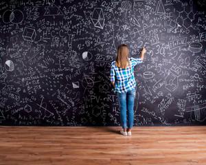 Student writing on big blackboard with mathematical symbols