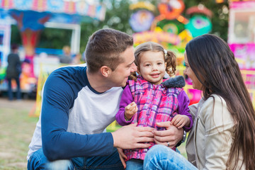 Father, mother and daughter having fun in amusement park