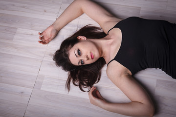 portrait of a beautiful woman lying on the wooden floor