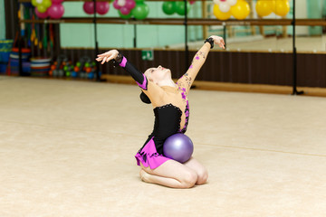 Young female gymnast doing crafty trick with ball