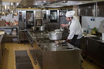 chefs cook and move around in the restaurant kitchen