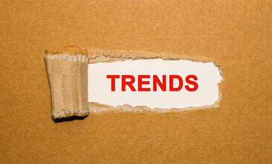 The text Trends appearing behind torn brown paper
