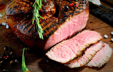 steak and rosemary on a wooden background