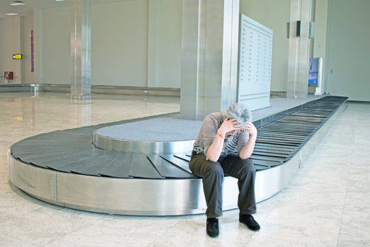 lost luggage - woman flight passenger frustrated sitting on empty luggage carousel waiting for baggage