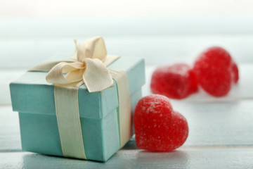 Gift box and  jelly hearts on color wooden background