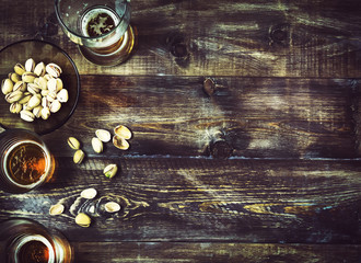 Beer, glass, pistachios on a wooden table. Beer background, top