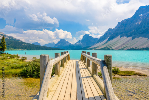 Wall mural Majestic mountain lake and small wooden bridge in Canada.