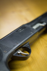 Close-up shotgun or gun on the old wood table (focus on trigger,