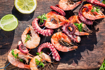Fresh skewers of seafood with lemon and parsley in garden