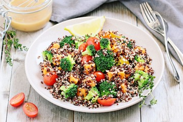 Quinoa salad with broccoli,sweet potatoes and tomatoes on a rustic wooden table.Superfoods concept.Selective focus.