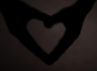 Hand shaped heart on dark background