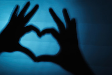 Hand shaped heart on blue wooden background