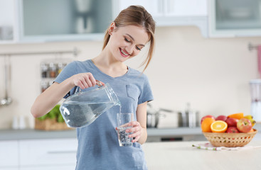 Young woman pouring water from jug into glass in the kitchen