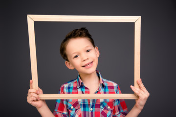 Cheerful young little boy holding wooden frame
