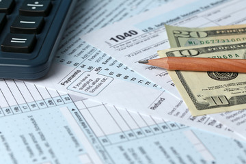 1040 Individual Income Tax Return Form for 2015 year with a pencil to fill in, calculator and dollar bills, close up