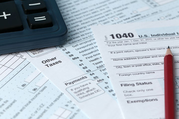 1040 Individual Income Tax Return Form for 2015 year with a pencil to fill in calculator, close up