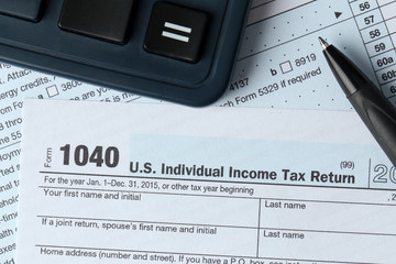 1040 Individual Income Tax Return Form for 2015 year with a pen to fill in and calculator, close up