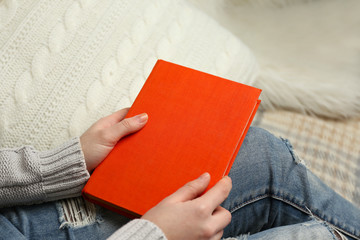 Young woman sitting on the sofa with white cushion and holding an orange book cover on her knees, close up