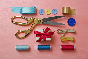 Sewing creative accessories on pink surface, top view