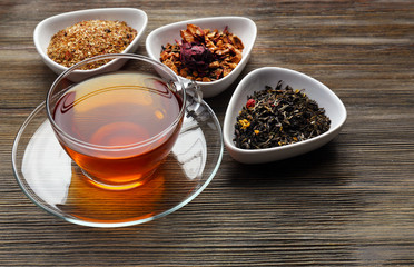 Tea concept. Different kinds of dry tea in ceramic bowls. Glass cup of tea on wooden background